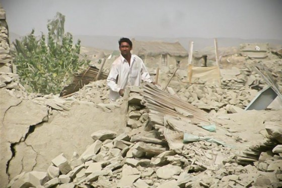 A man in Balochistan's Awran district taking his belongings from the rubble of his demolished house.