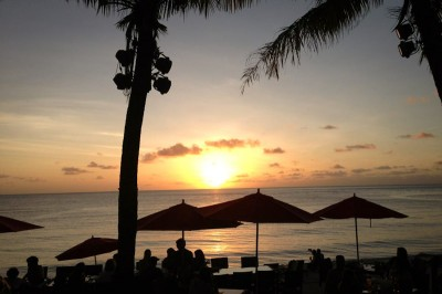 The sun sets as tourists, locals, and military members drink at The Beach Bar at Gun Beach facing the Philippine Sea. (Photo by Michelle Conerly)