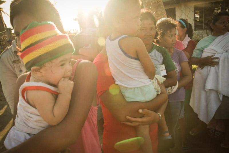 Women and children receive typhoon relief aid last month. (Photo courtesy Balsa Mindanao)