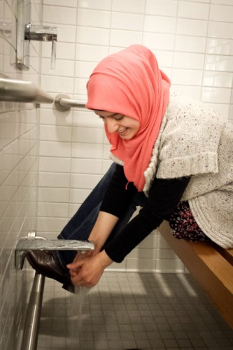 Meva Beganovic completes the traditional Muslim ablution procedure before entering the prayer room at the UW HUB. (Photo by Annie Wilson)