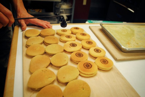 Art Oki meticulously prepares dorayaki, a cake-flour dessert with red bean paste, branded with an emblematic chrysanthemum.  (Photo by Anna Goren)