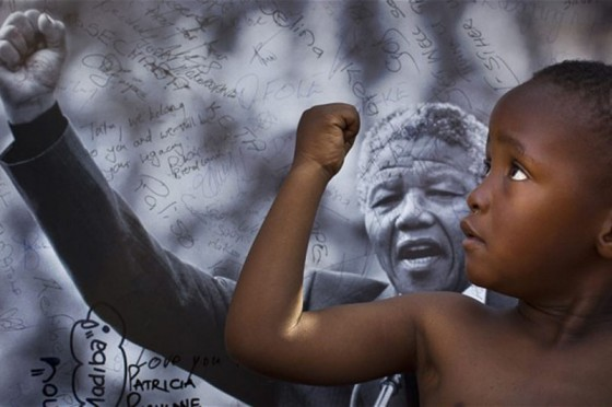 A young boy from the Maitibolo Cultural Troupe pays tribute to former South African President Nelson Mandela in Pretoria, South Africa. (Photo by Ben Curtis/Associated Press)
