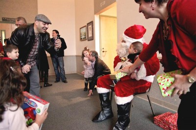 Santa Claus gives out presents to children after Sunday services at Saint Joseph, a church with members from across the Middle East including Syria, Lebanon and Jordan. (Photo by Sara McCaslin)