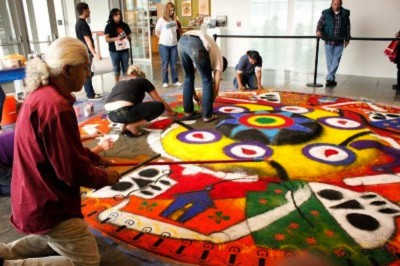 Artist Victor Gonzalez helped assemble a sand carpet designed by Oaxacan artist Fulgencio Lazo, following the Dia de los Muertos tradition of his region of Mexico. (Photo by Liliana Caracoza)