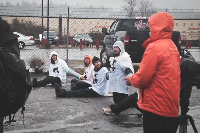 Activists chain themselves together to block deportation vans in Tacoma on Monday. (Photo by Jill Mangaliman)