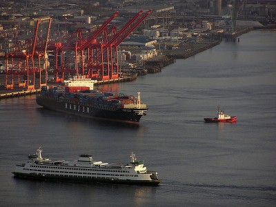 A container ship sails away while the Bainbridge Island ferry enters the Port of Seattle. (Photo via Wikipedia)