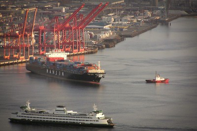 A container ship leaves the Port of Seattle while the Bainbridge Island ferry enters. (Photo via Wikipedia)