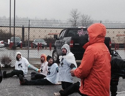 Activists chain themselves to block deportation vans in Tacoma on Monday. (Photo by Jill Mangaliman)