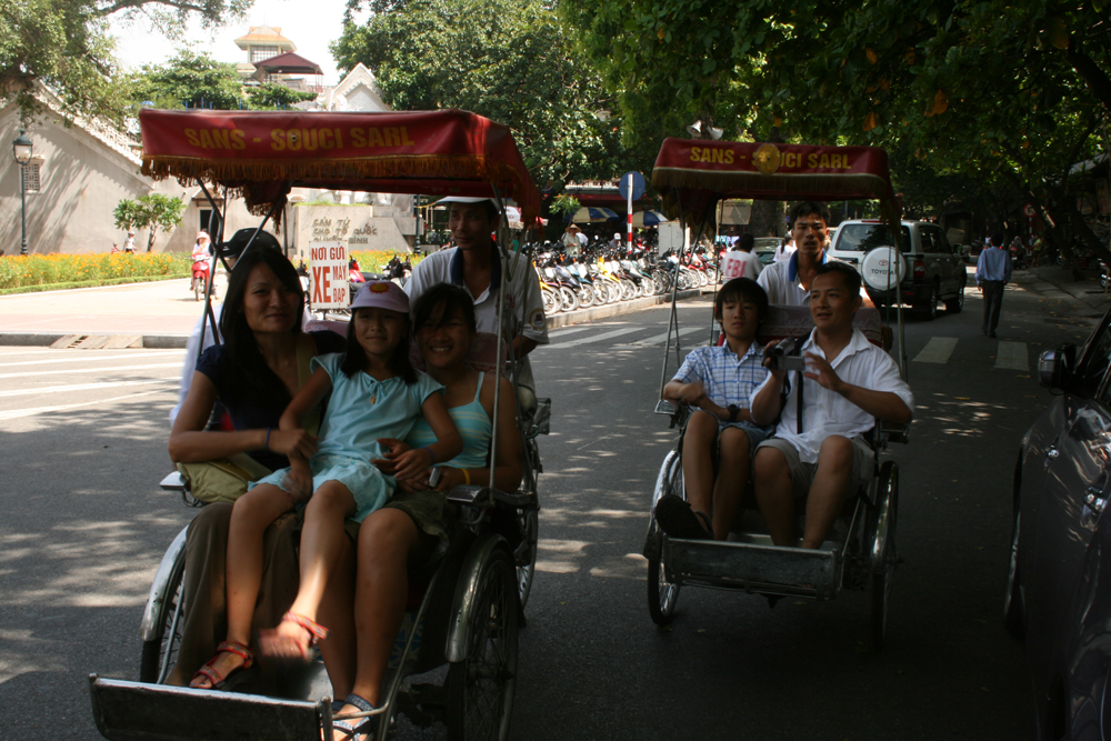 The author (second from right) riding city pedicabs with his family in Saigon, Vietnam in 2007.