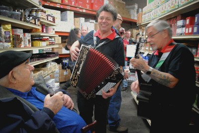Lennu Luzzi and his band serenade John Croce (left) with familiar Italian songs during his 90th birthday celebration in the store. (Photo by Anna Goren)