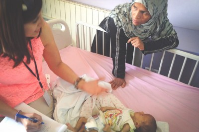 A refugee in Bekaa ITS discusses care for her malnourished child with a volunteer. (Photo by Karin Huster)