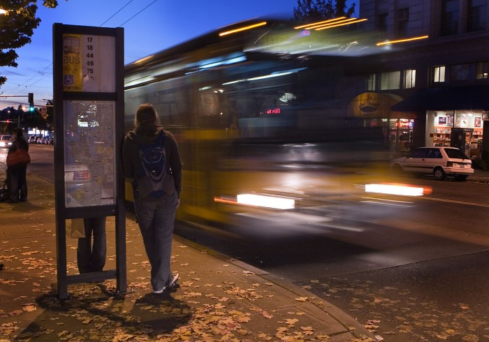 A rider waits at a bus stop in Seattle.