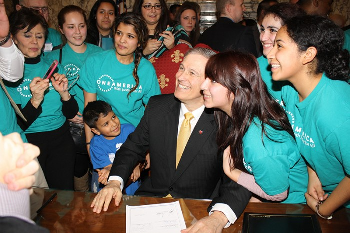 Gov. Jay Inslee signing the Washington State Dream Act. (Photo thanks to OneAmerica)