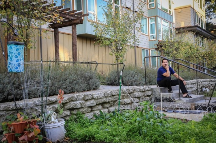 Amer Kuba sits outside his home in North Seattle (Photo by Laura Huysman)