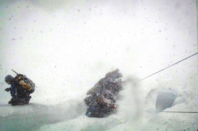 Climbers in the midst of a small avalanche during an Everest ascent. (Photo by Lloyd Smith)