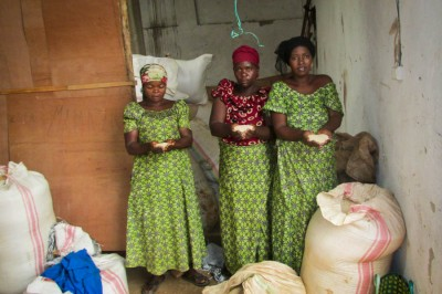 Three of the women from the Carama Women's Association, posing with what's left of rice reserves after flooding hit their homes in February. (Photo by Prosper Ndabishuriye)