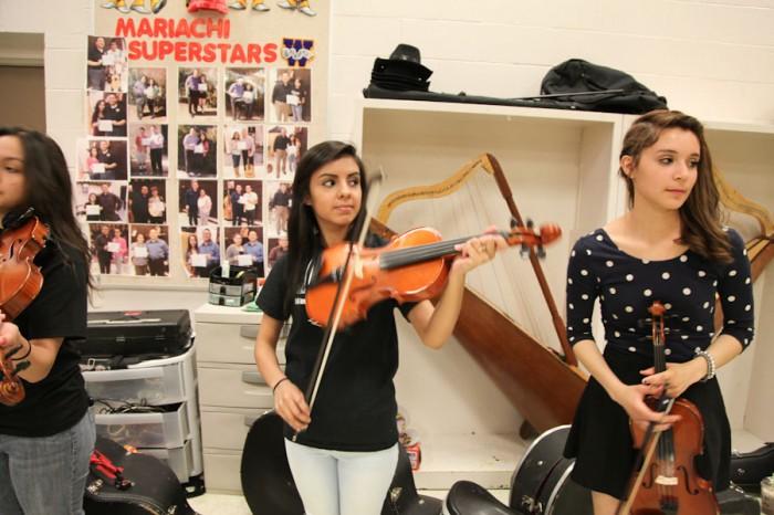 Mailarie Muñoz, age 16 (center) and Jennifer Bravo, age 16 (right), during the intermediate Mariachi class program at Wenatchee High School. (Photo by Alex Stonehill)
