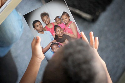 """Dede Adhanom's son King holding family photo in a still from """"Unified Struggle."""" (Courtesy of Guerrilla Films)"""