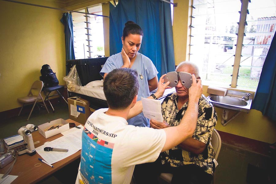 A medical interpreter assists a patient in Tonga during an eye exam. (Photo by Mass Communication Specialist 2nd Class Joshua Valcarcel / U.S. Navy)