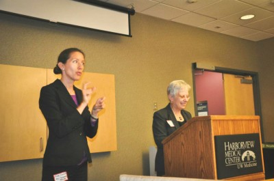 Joana Ramos (right) speaks at a conference at Harborview Medical Center, with an ASL interpreter by her side.(Photo courtesy WASCLA)