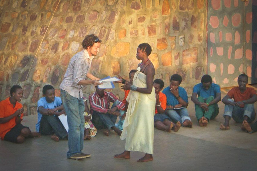 The author presenting an award to student Jocelyn following the performance of Making Peace in Old Village, August 2012. (Photo by Erika Rose)