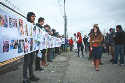 Protestors hold up wall of photos of those locked up & deported