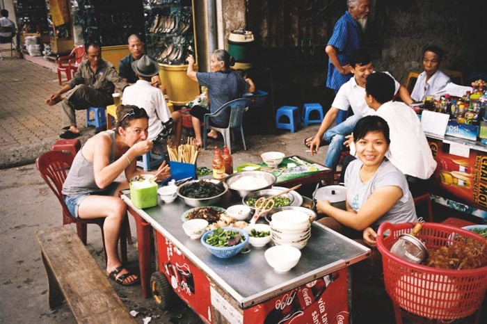 """Backpacker enjoying street food at a curbside cafe in Haiphong. (Photo from Flickr by<a href=""""https://www.flickr.com/photos/hramirez/""""> HRamirez</a>)"""