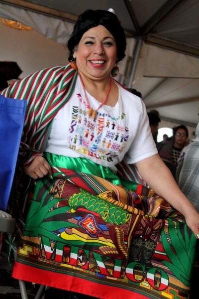 "Martha Camarena shows her skirt which reads ""Mexico!"" Camarena is originally from Guadalajara, Mexico and participates in performances and events with El Centro de la Raza."