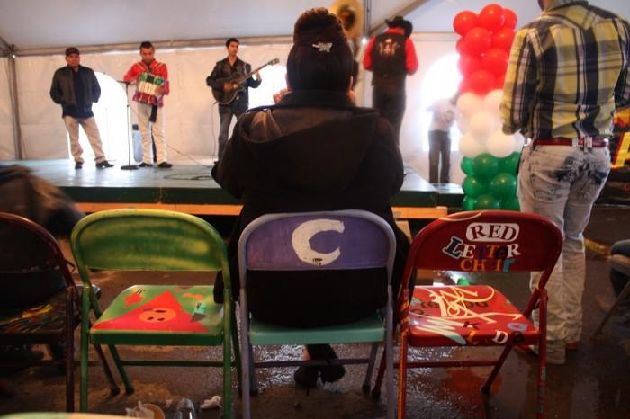 A visitor films a performance by Tigre Vazquez y su Banda during Cinco de Mayo at El Centro de la Raza.