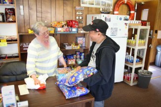 Betty Erichsen, a volunteer at the Tacoma Seafarers' Center, helps Filipino seafarer Rommel Quibaez with a bulk candy bar purchase. Seafarers are typically in port for about 12 hours only once every few weeks, so an opportunity to stock up on essential items is welcome. (Photo by Alex Stonehill)