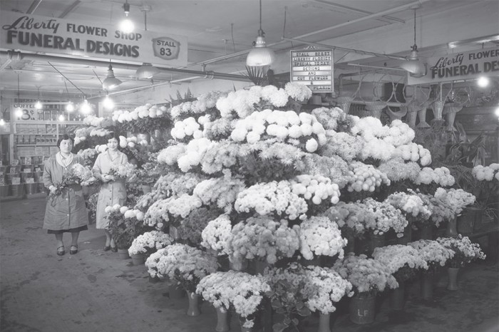 "A Japanese-American-owned Liberaty Flower Shop at Pike Place Market, ca.1931. By fall of 1907, nearly 80% of the stalls were operated by Japanese farmers. The photo is part of the ""Grit"" exhibit at the Wing Luke Museum. (Photo courtesy of Washington State Historical Society)"