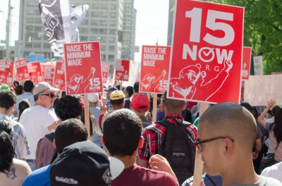 Nearly 10,000 showed up the May Day march with signs and flags, calling for a higher minimum wage and an end to discrimination against immigrants. (Photo by Seth Halleran)