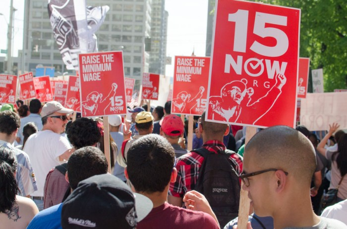 Participants in a May Day march in Seattle in 2014 carry signs and flags calling for a higher minimum wage. (Photo by Seth Halleran)