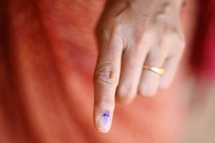 Election ink is applied to a voter's index finger after casting their ballot in the Lok Sabha elections in India. (Photo by Jane D'Souza)