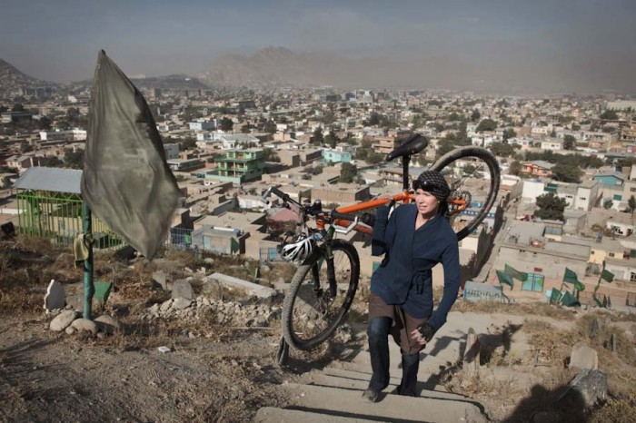 Shannon Galpin carries her bike up a hill outside Kabul. (Photo courtesy mountain2mountain.org)