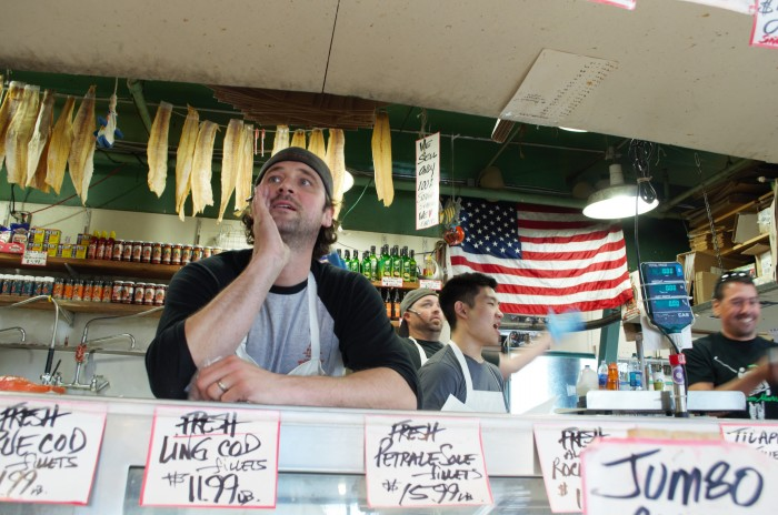 Anders Miller, assistant manager at Pike Place Fish Market, yells to encourage people to buy fish. (Photo By LaVendrick Smith)