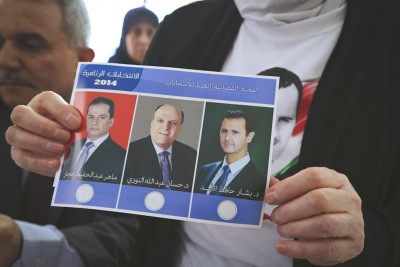 A Syrian refugee in Beirut holds a ballot from Tuesday's multiparty presidential elections. Bashar Al-Assad (right) is almost assured victory. (Photo from Reuters)