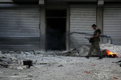 A member of the Free Syrian Army walking among the rubble in Aleppo in 2012. The opposition to the Assad regime has split into several factions as the war drags on. (Photo via Wikipedia)