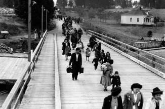 Japanese Americans walk down the Bainbridge Islan ferry dock to catch a special ferry to Seattle for mass removal in 1942. (Photo courtesy of the Museum of History & Industry)