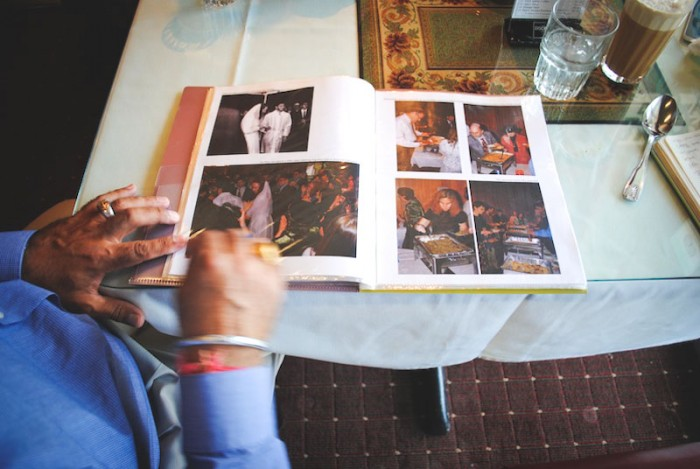 Hanek flips through a photo album of the first orthodox Jewish wedding in Portland catered by Pabla. The album is featured prominently upon entering, titled 'Jewish Wedding with Pabla Indian Cuisine.' (Photo by Anna Goren)