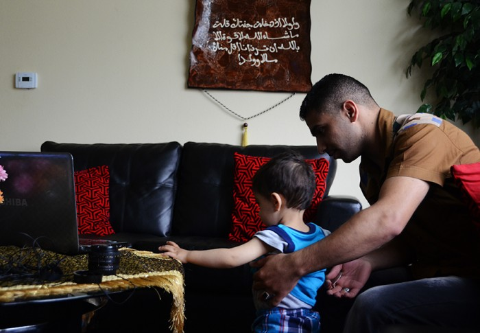 Ali Al-Khazaraji plays with his youngest brother in their home in Kent. (Photo by Alisa Reznick)