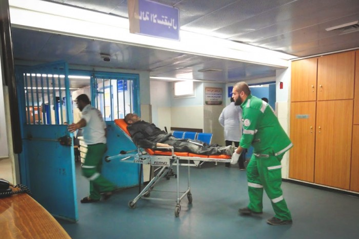 EMTs bring a patient into Al Shifa Hospital. (Photo by Karin Huster)