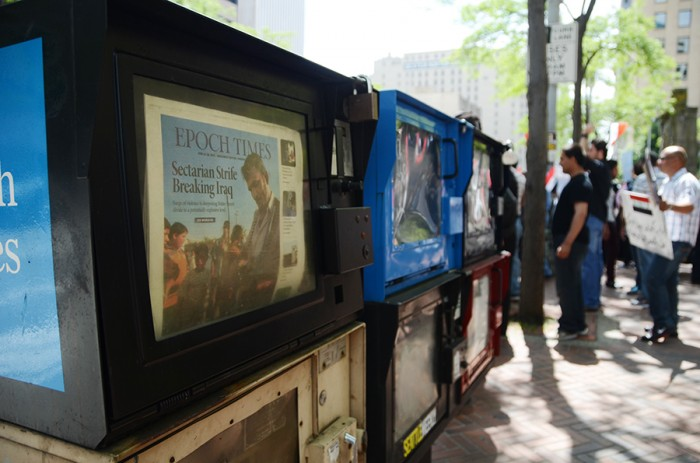 Protesters stand in front of Seattle's City Hall downtown, beside them a newspaper stand displays an article about the sectarian situation unfolding in Iraq. (Photo by Alisa Reznick)