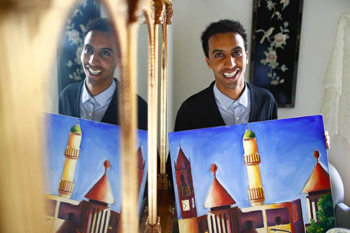 "Abraham Tesfasilasie, 21, holds his oil painting entitled, ""United"", at his apartment in Seattle. Tesfasilasie, along with a friend and fellow artist, is putting on an art show on July 10th to help raise money to perform dental work he needs. The art piece depicts a scene from Asmara, the capitol of Eritrea, where he is from. (Photo by John Lok / The Seattle Times)"