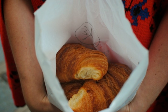 The author holds a bag of croissants, still cheap in an otherwise exorbitant country. (Photo by Molly Goren).