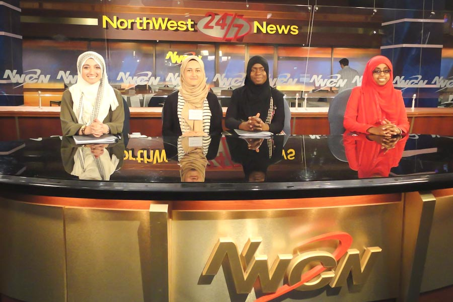 Participants in the Muslim Youth Leadership Program pose for a photo behind the Northwest Cable News desk. (Photo courtesy CAIR-WA)
