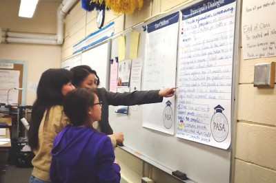 Mai Tran (rear) working with Vietnamese families to select questions to be asked during a dialogue with on of the Kent School District's principals. (Photo courtesy of Millicent Borishade)