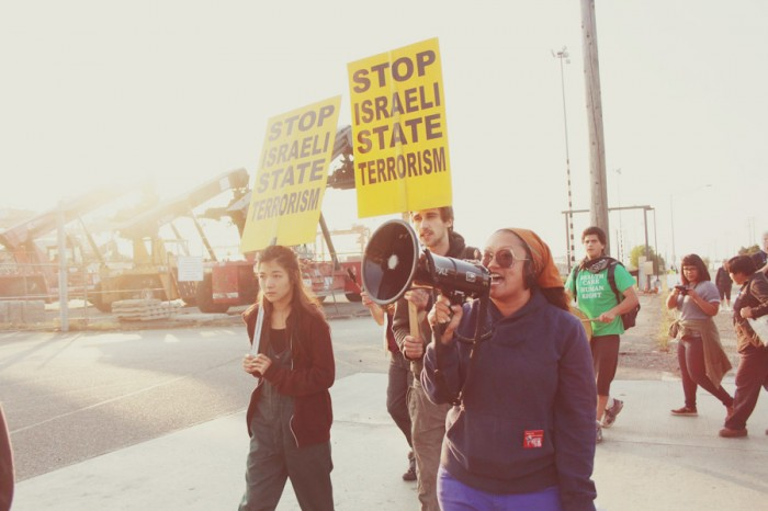 Katrina Pestaño (with bullhorn) at the Port of Tacoma Saturday morning during a protest action to delay the unloading of cargo from an Israeli shipping company. (Photo by Derek Dizon)