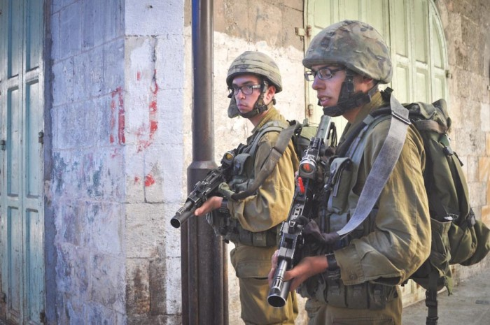 Israeli soldiers patrol a Palestinian protest in Hebron earlier this month. (Photo by Thomas James)