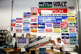 The wall of old signs inside of Thompson Signs' warehouse serves as a visual reminder of the mostly white, male political candidates in the northwest. (Photo by Lucas Anderson / UW Election Eye)